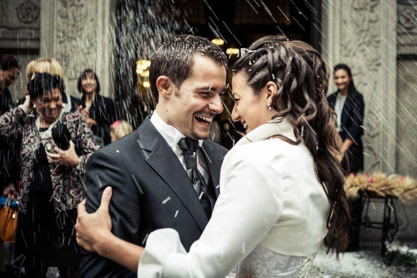 Due sposi sorridono durante il momento del lancio del riso - Fotografo matrimonio Torino
