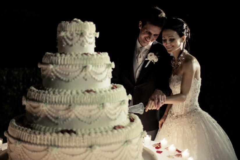Due sposi sorridono mentre tagliano la torta