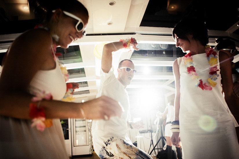 Fotografo matrimonio Torino: gli invitati in bianco ballano sul battello fluviale a Torino