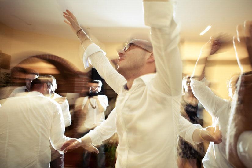 Fotografo matrimonio Torino: il testimone balla con le mani al cielo