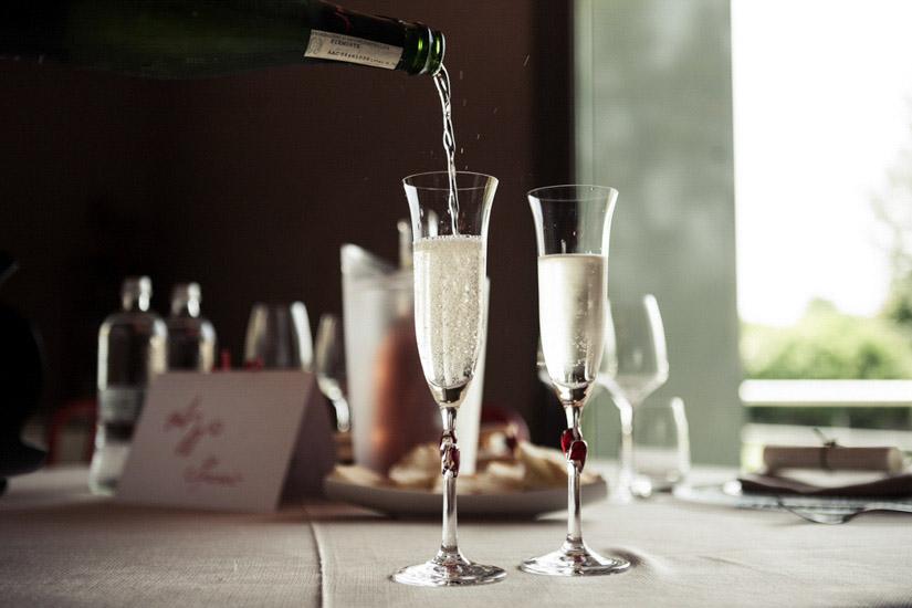 Fotografo matrimonio Torino: il cameriere versa lo champagne nei calici degli sposi per il brindisi