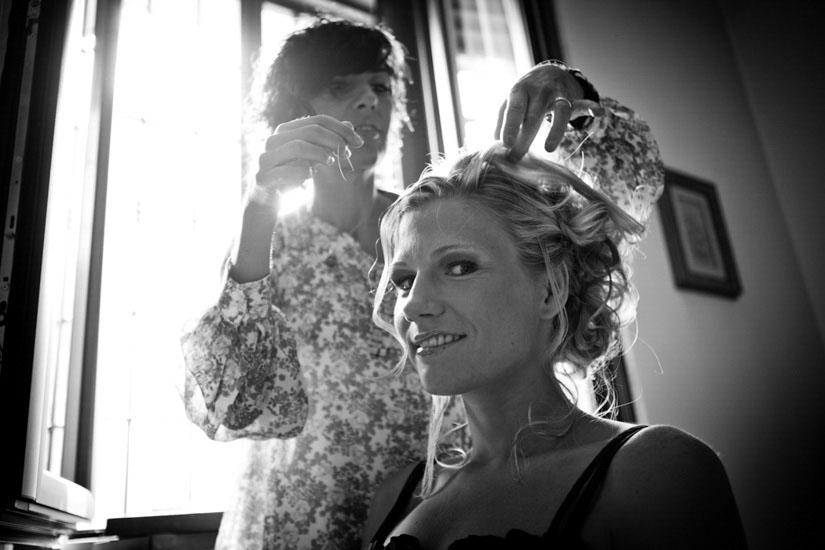 Fotografo matrimonio Torino: una parrucchiera agghinda la testa della sposa bionda