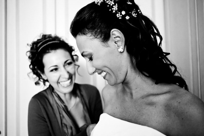 Fotografo matrimonio Torino: la testimone veste la sposa a scherza con lei