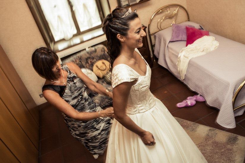 Fotografo matrimonio Torino: una mamma aiuta sua figlia a vestirsi per il suo matrimonio