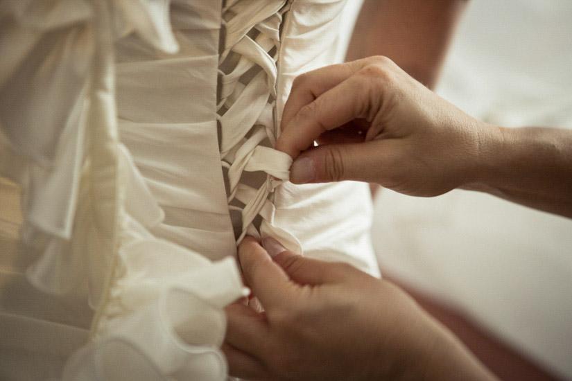 Fotografo matrimonio Torino: preparativi per l'allacciamento del vestito da sposa