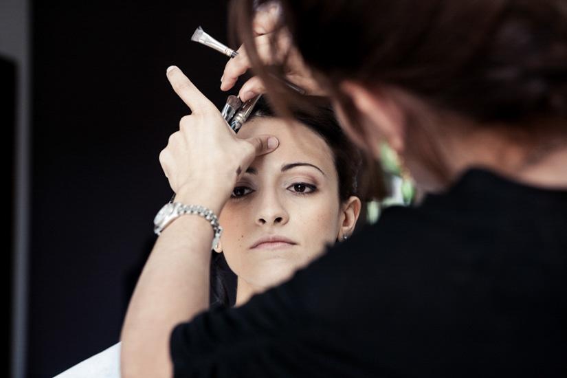 Sapienti mani curano l'aspetto della sposa perché tutto sia perfetto