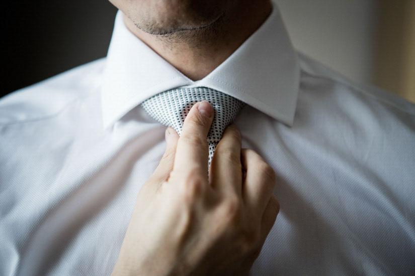Fotografo matrimonio Torino: una mano stringe la cravatta per terminare i preparativi per il matrimonio
