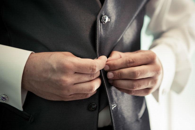 Fotografo matrimonio Torino: lo sposo si chiude i bottoni del gilet ed è pronto per il suo matrimonio