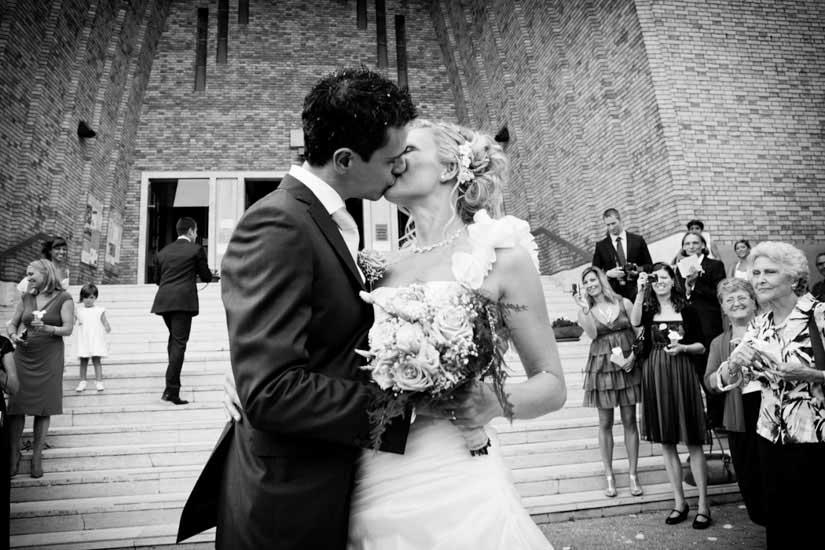 Fotografo matrimonio Torino: due sposi si baciano sul sagrato di una chiesa a Torino