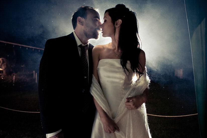 Due sposi si baciano sotto la pioggia
