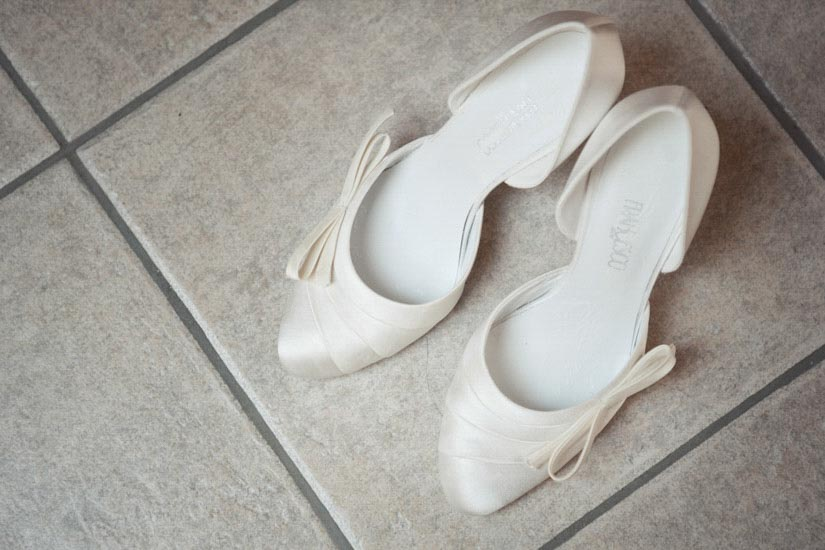 Fotografo matrimonio Torino: due scarpe bianche per un vestito da sposa a Pecetto